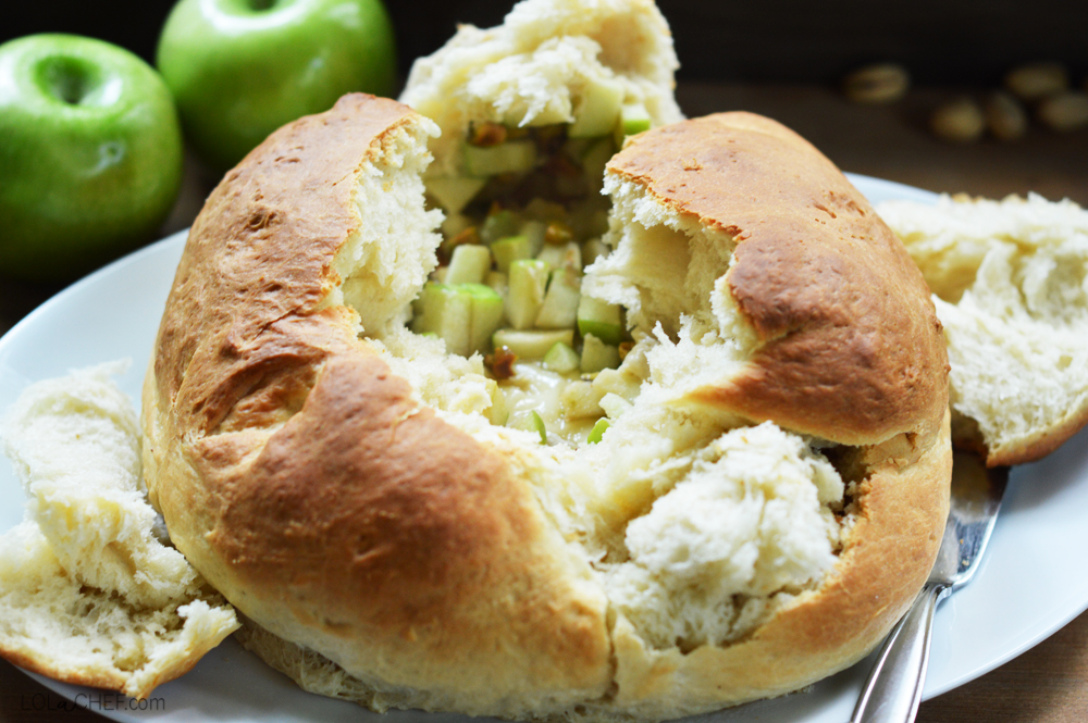 An easy baked brie recipe that is baked in a bread bowl with apples, honey, and pistachios.
